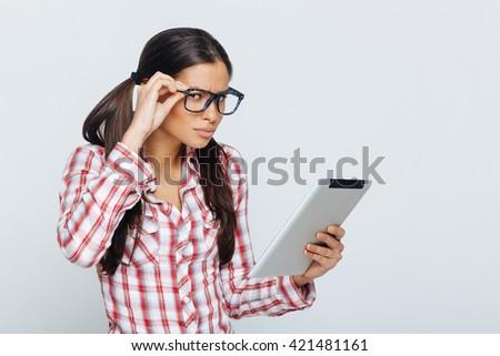 Beautiful geek woman holding digital tablet in studio on white - stock photo