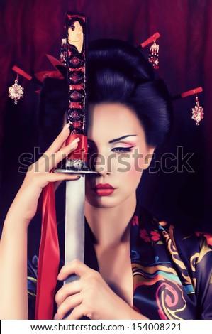 Beautiful geisha in kimono with samurai sword - stock photo