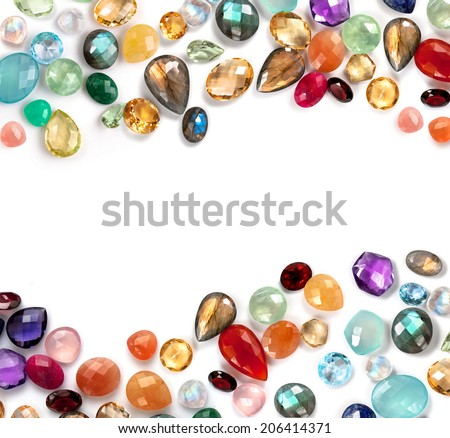 Beautiful gems composition with empty space in the middle. Bright real gems: labradorite, ruby, amethyst, blue topaz, citrine, rose quartz, garnet, moonstone rainbow, prehnite... on white background. - stock photo