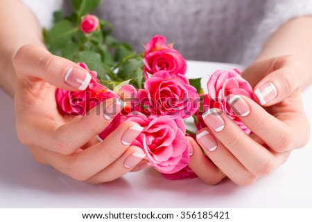 Beautiful gentle french manicure with pink roses close-up.