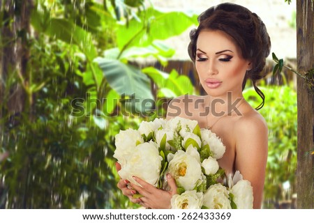 Beautiful gentle slim sexy dreaming brunette woman staying naked with bunch of flowers under the warm tropical rain in jungle forest background with copy space. Spa beauty and healthy life concept - stock photo