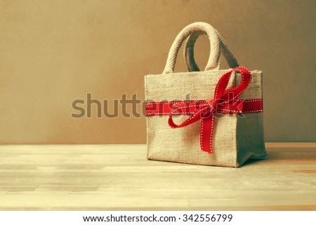 Beautiful gift bag with red bow on wood background and color filters - stock photo