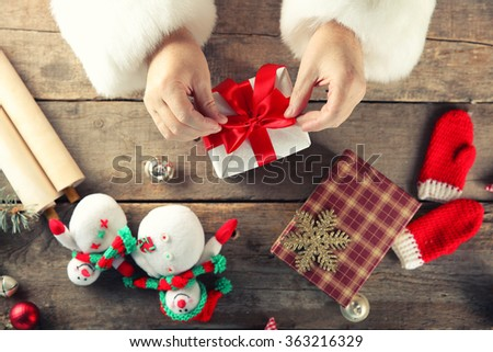 Beautiful gift box in Santa Claus's hands and Christmas decorations on wooden table, close up