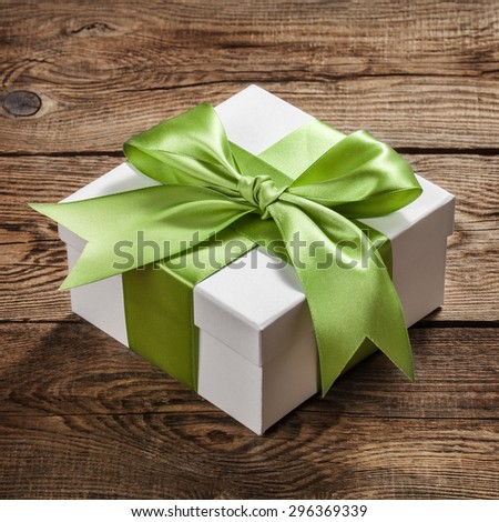 Beautiful gift box with a bow on the table from the old boards. - stock photo