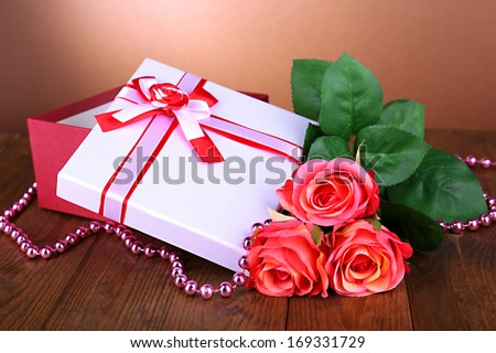 Beautiful gift box with flowers on table on brown background