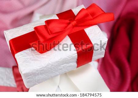 Beautiful gift with red ribbon on pink cloth