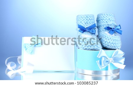 beautiful gifts, baby's bootees, blank postcard and dummy on blue background
