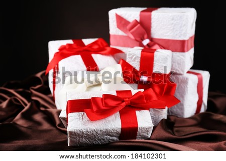 Beautiful gifts with red ribbons on silk, on dark background - stock photo