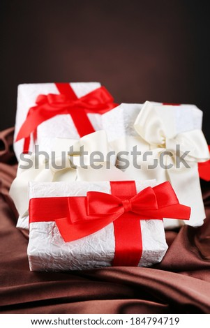 Beautiful gifts with red ribbons on silk, on dark background