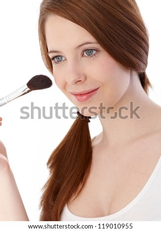 Beautiful ginger girl applying makeup with brush, smiling, looking away. - stock photo