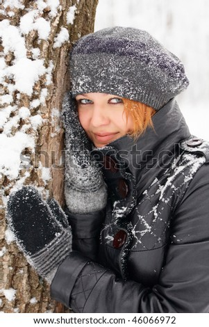 Beautiful ginger-haired girl near a tree - stock photo