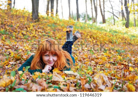 Beautiful ginger-haired woman lying on a blanket of fall leaves