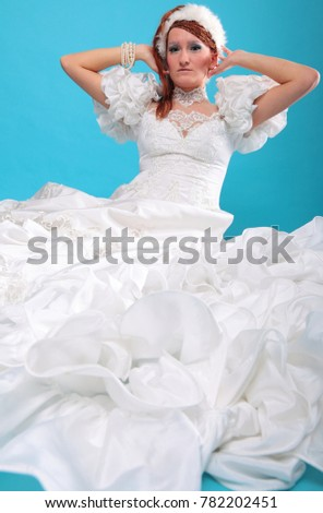 Beautiful ginger in white dress of Snow Queen blue background