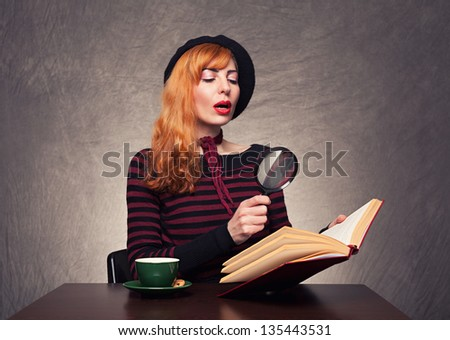 beautiful ginger model reading a book with her magnifying glass on grunge background - stock photo