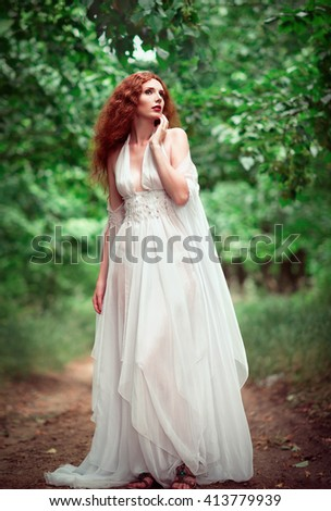 Beautiful ginger woman wearing white dress in the grove - stock photo