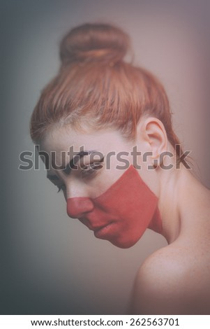 Beautiful ginger woman with red face paint. Retro tones - stock photo