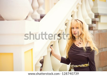 beautiful girl a blonde stands near architectural elements