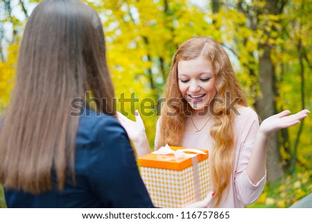 Beautiful girl accepting a gift on her birthday - stock photo