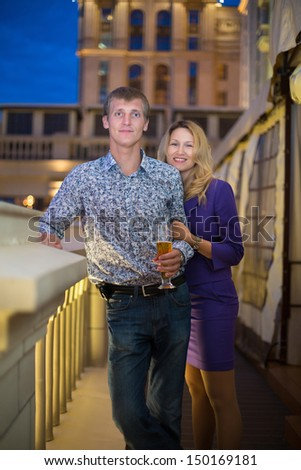 Beautiful girl and a guy with a beer in the evening
