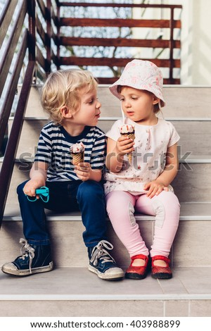 Beautiful girl and boy eat ice cream on the stairs - stock photo