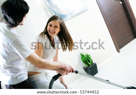 Beautiful girl and boy with vacuum cleaner
