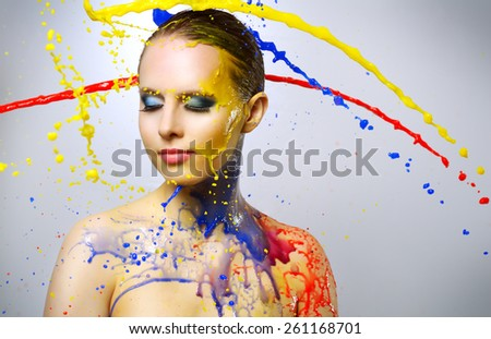 Beautiful girl and colorful paint splashes on light background - stock photo
