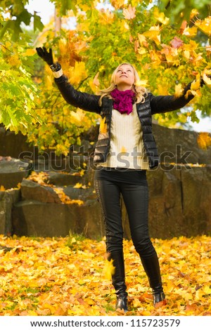 Beautiful girl and falling leaves, autumn color, vertical format - stock photo