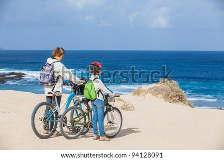 Beautiful girl and her grandmother on bikes on the beach. Lanzarote - stock photo