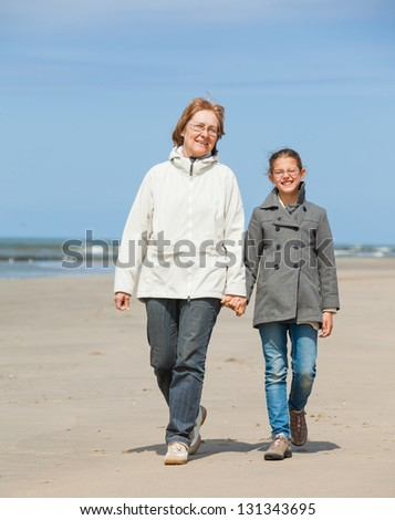 Beautiful girl and her grandmother walking on the beach. Holland