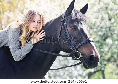 Beautiful girl and horse in blossoming spring garden - stock photo