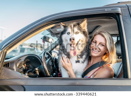Beautiful girl and husky sitting in a car and looking at camera - Funny dog with owner in a car - stock photo