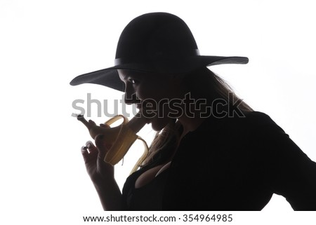 Beautiful girl and yellow banana - A beautiful brunette with gray old bowler hat on her head with a black jacket naughty kissing and licking fresh yellow raw banana - facial expressions - stock photo