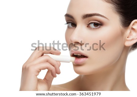 Beautiful girl applying chapstick - stock photo