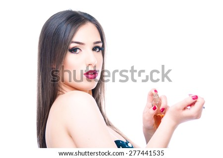Beautiful girl applying perfume on her hand and looking into camera, isolated on white - stock photo