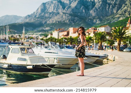 beautiful girl at quay with yachts  - stock photo