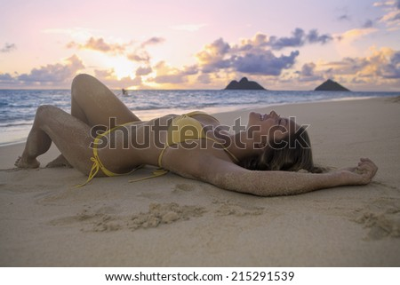beautiful girl at the beach at sunrise in hawaii