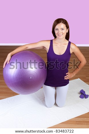 Beautiful girl at the gym holding a balance ball