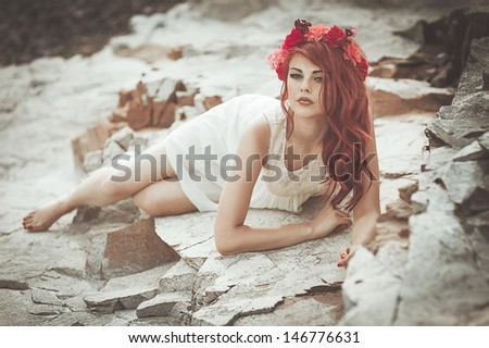 beautiful girl  at  the mountains wearing a ringlet of flowers - stock photo