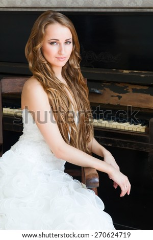 Beautiful girl at the piano - stock photo