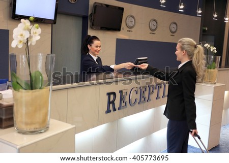Beautiful girl at the reception of a hotel checking in. - stock photo