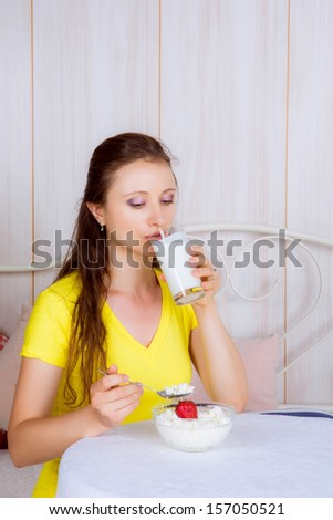 beautiful girl at the table eating dairy products and drinking milk - stock photo