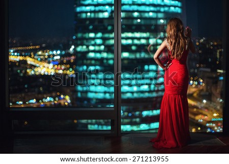 Beautiful girl at the window at night - stock photo