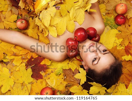 Beautiful girl Autumn lying over yellow leaves carpet - stock photo