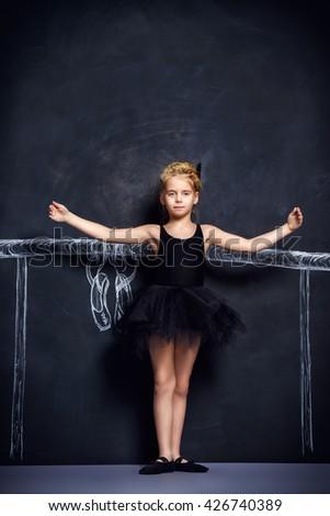 Beautiful girl ballet dancer in black leotard and tutu posing in studio over black background. - stock photo