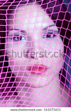 beautiful girl behind the net