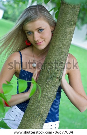 beautiful girl between trees in the garden