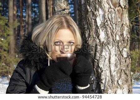 beautiful girl blonde drinking tea in winter - stock photo