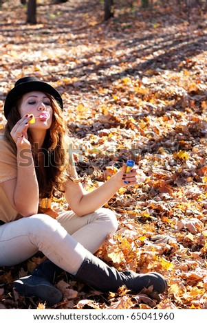 Beautiful girl blow bubbles on the background of the yellow fallen leaves