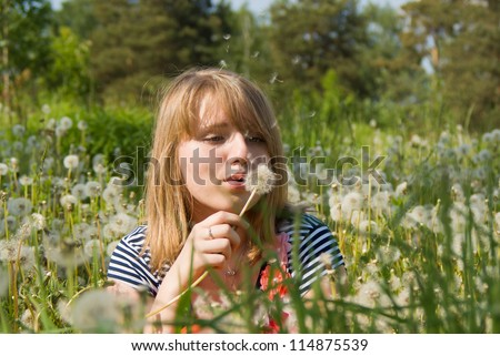 beautiful girl blow on the dandelion on nature