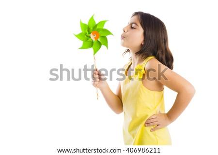 Beautiful girl blowing a plastic windmill - stock photo